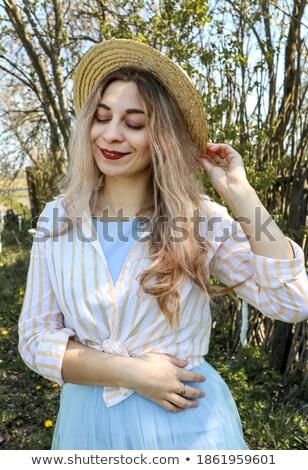 portrait of a woman in hat made of flowers stock photo © konradbak