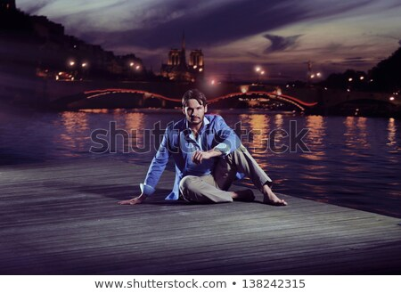 Elegant young handsome man over night city background stock photo © konradbak