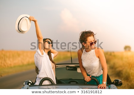 Foto stock: Two Young Happy Girls Having Fun In The Cabriolet Outdoors