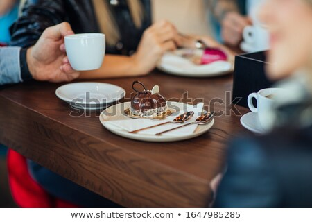Friends sitting in cafe. Focus on food. stock photo © deandrobot