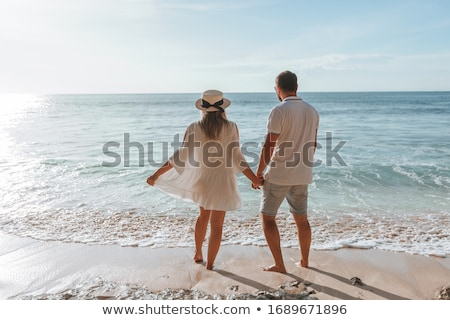happy young romantic couple relaxing on the beach and watching the sunset stock photo © master1305