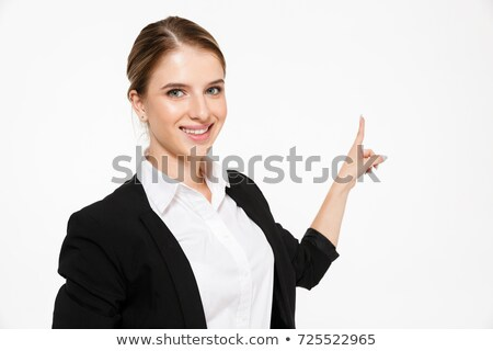 Smiling blonde business woman pointing back and looking at camera Stock photo © deandrobot
