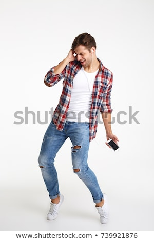 full length portrait of a cheery young man with earphones stock photo © deandrobot