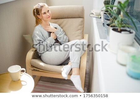 blonde casual woman sits on stool and looks to side Stock photo © feedough