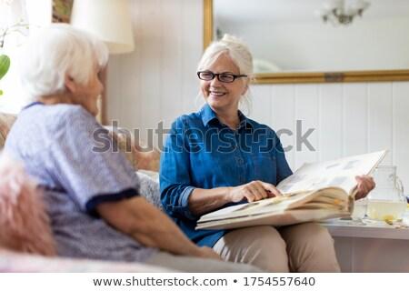 Idős nő néz család album nappali Stock fotó © IS2