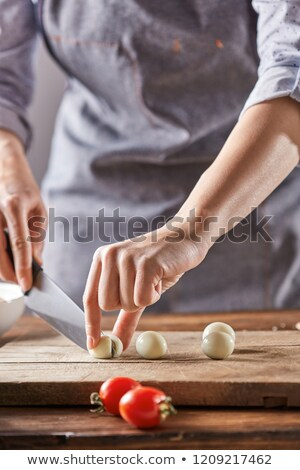 Cook woman in a gray apron cuts boiled quail eggs on a wooden board. Step by Step Cooking Stock photo © artjazz