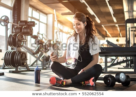 Young  fit sporty woman resting and listen music on mobile phone stock photo © boggy