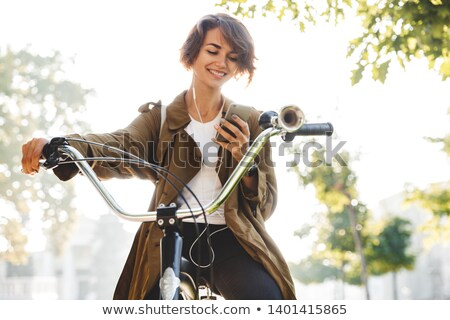Cute young woman walking in park with bicycle listening music with earphones. Stock photo © deandrobot