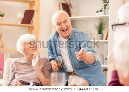 Happy senior man with flute of champagne pointing at his friend Stock photo © pressmaster