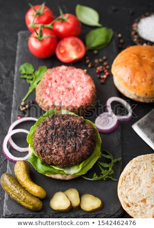 Stockfoto: Fresh Grilled And Raw Minced Pepper Beef Burger On Stone Chopping Board With Buns Onion And Tomatoes