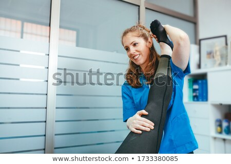 Physiotherapist Stretching Leg Of Girl Patient Stock photo © AndreyPopov