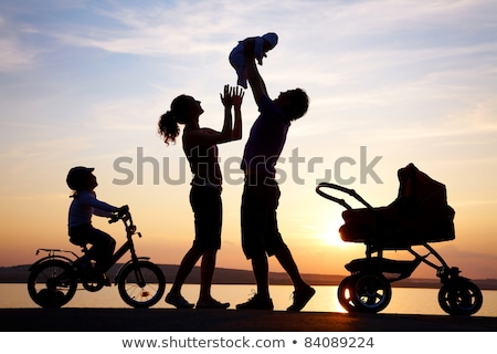 Silhouettes of parents loving  their child in a stroller Stock photo © Lopolo