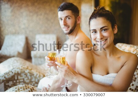 Pretty young relaxed woman with flute of champagne lying in empty bathtub Stock photo © pressmaster