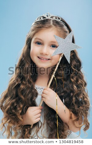 Photo of small fairy girl with curly dark hair, wears crown and dress, has blue eyes, gentle smile,  Stock photo © vkstudio