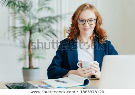 Pleasant looking elegant female freelancer books items on web store, reads news in internet, writes  Stock photo © vkstudio