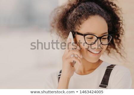 Close up portrait of cheerful woman with crisp hair, satisfied with tariffs for telephone call, focu Stock photo © vkstudio