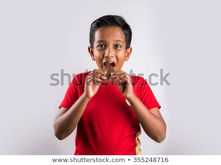 boy eat chocolate in front of a white background Stock photo © Lopolo