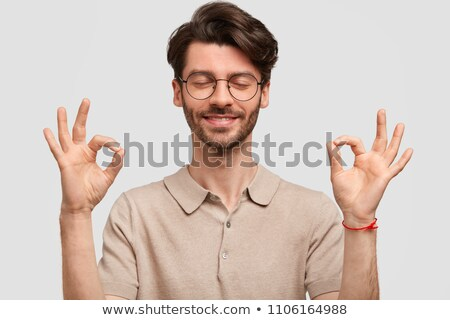 Portrait of hppy bearded male makes eyewear with fingers, has st Stock photo © vkstudio