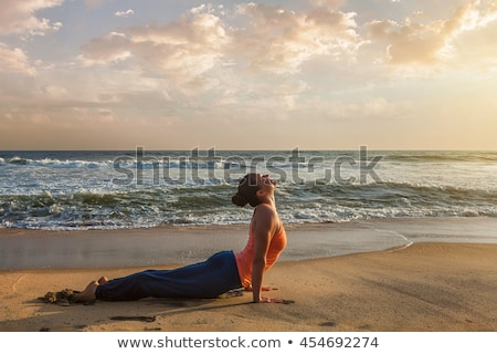 Woman practices yoga asana Urdhva Mukha Svanasana outdoors Stock photo © dmitry_rukhlenko