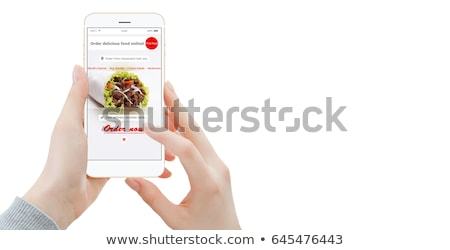 Young woman orders food for lunch online using a smartphone Stock photo © galitskaya
