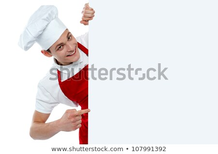 Stock photo: Male chef indicating at blank menu