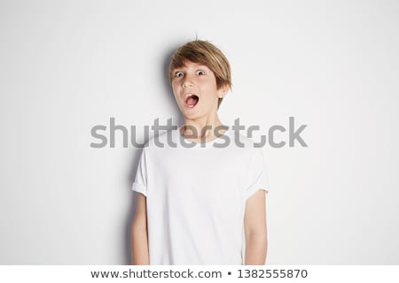Portrait of a happy boy smiling at the camera with the thumb up against a white background stock photo © wavebreak_media