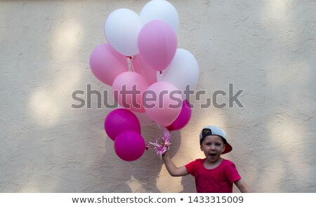casual man with balloons holds hand in pocket stock photo © feedough