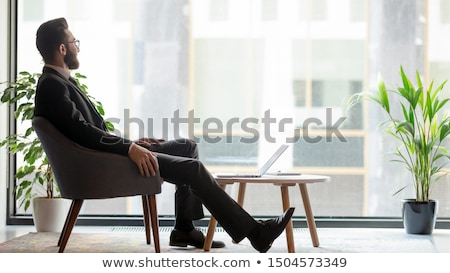 elegant business man sitting and looking to his side stock photo © feedough