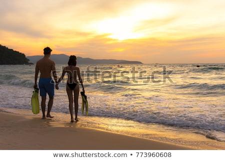 Woman in bikini with snorkelling gear walks on beach  Stock photo © Kzenon