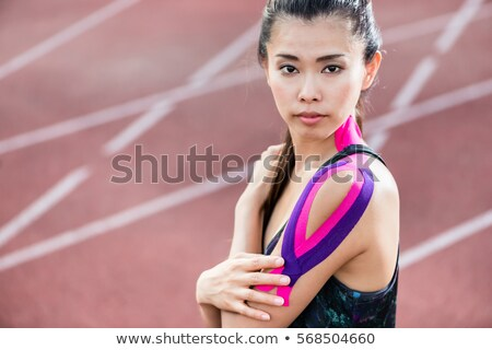 woman taping with therapeutic tape on cinder track of sports sta stock photo © kzenon