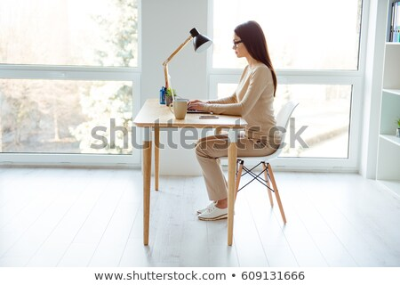 Side view of woman sitting by the table Stock photo © deandrobot
