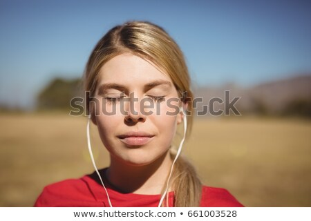 Woman listening music on headphones during obstacle course Stock photo © wavebreak_media