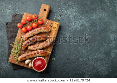 grilled sausage on dark rustic wooden background top view stock photo © yelenayemchuk