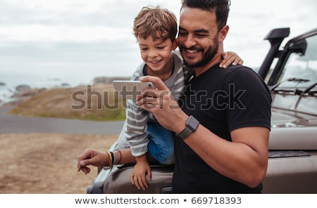 Handsome smiling child boy holding mobile phone or smartphone selfie stick taking portrait photo Stock photo © ia_64