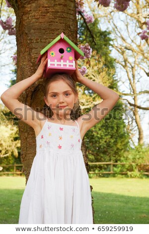 Girl holding birdhouse on her head Stock photo © IS2