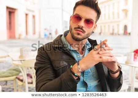 fashion man with leather jacket sitting and praying Stock photo © feedough