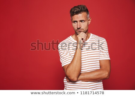 Unshaved man in striped t-shirt thinking and touching chin, isol Stock photo © deandrobot