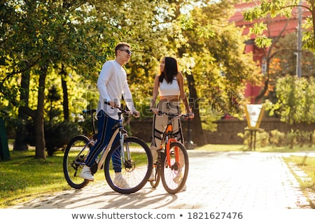Smiling young woman bicyclist spending time at the park Stock photo © deandrobot
