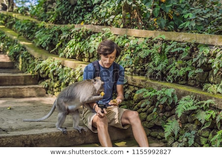 Selfie with monkeys. Young man uses a selfie stick to take a photo or video blog with cute funny mon Stock photo © galitskaya