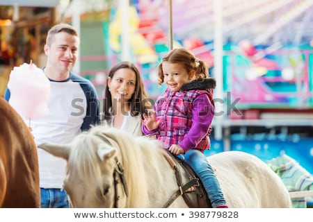 cute little girl enjoying in funfair and riding on colorful carousel house banner long format stock photo © galitskaya