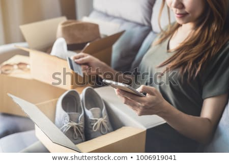 young woman received online shopping parcel opening boxes and buying fashion items by using credit c stock photo © galitskaya