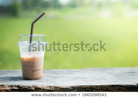 Green tea latte with ice in plastic cup and straw in female hand with yellow manicure on yellow back Stock photo © galitskaya
