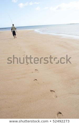 Man Walking Along Shore Of Beach Carrying Fishing Rod Stock photo © monkey_business