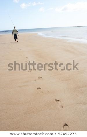 man walking along shore of beach carrying fishing rod stock photo © monkey_business