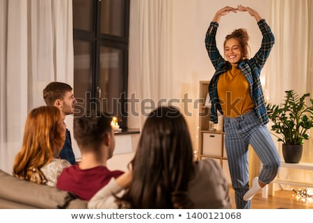 happy friends playing charades at home in evening Stock photo © dolgachov