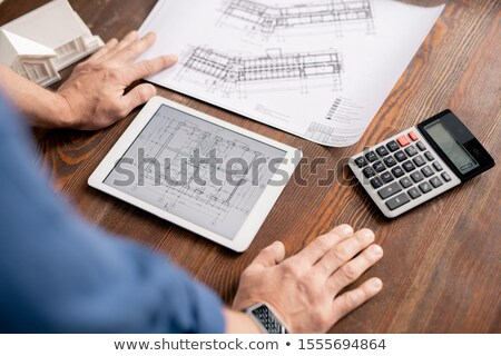 Hands of modern engineer leaning on wooden table while bending over tablet Stock photo © pressmaster
