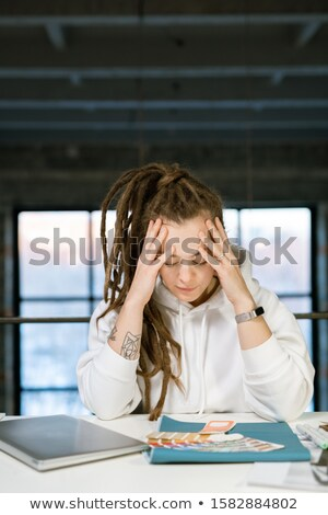 Pensive female designer touching her head while concentrating on work Stock photo © pressmaster