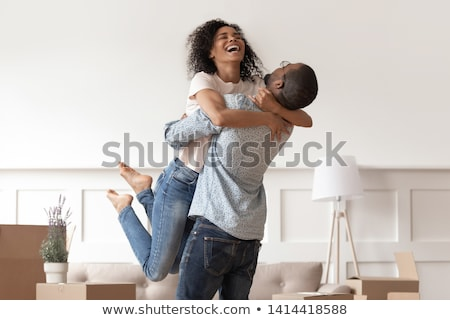 Affectionate family couple celebrate moving day, embrace and holds favourite pet, enjoy relocaton an Stock photo © vkstudio