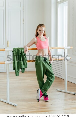 Fit ballet dancer in class near barre, rests on bar, has combed ginger hair, wears top and sport tro Stock photo © vkstudio