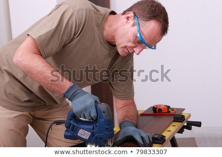 man using an electric saw to cut a wooden floorboard stock photo © photography33